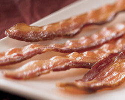Thick strips of bacon on a plate... what's better than that divine smell in the morning?